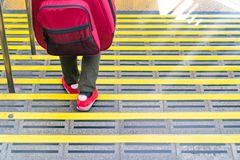 Japanese guy walking down the stair at the train station with the guitar backpack on his back royalty free stock image