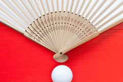 Japanese hand fan made and golf balls on the red table Stock Images