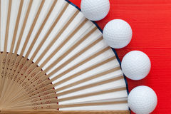 Japanese hand fan made and golf balls on the red table Royalty Free Stock Photos
