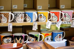 Japanese handmade ceramic cups with Doraemon characters style are displayed for sale in Doguyasuji arcade, Osaka, Japan. Royalty Free Stock Image