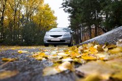 Japanese hatchback on autumn road. In rainy day Stock Photo
