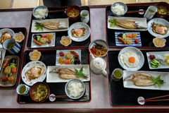 Japanese homestay breakfast tray including cooked white rice, grilled fish, fried egg, tofu soup, sausage, pickle, seaweed, etc. Japanese homestay breakfast Royalty Free Stock Image