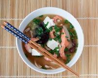 Japanese hot pot soup yosenabe. Bowl of japanese hot pot soup yosenabe with chopsticks on reed mat Royalty Free Stock Photo