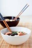 Japanese hot pot soup yosenabe. Two bowls of japanese hot pot soup yosenabe with chopsticks on reed mat Royalty Free Stock Image