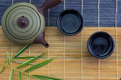 Japanese hot tea pot with cup on bamboo mat Royalty Free Stock Photography