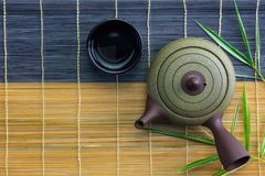 Japanese hot tea pot with cup on bamboo mat Royalty Free Stock Images