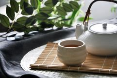 Japanese Hot Tea on Bamboo Mat. Japanese hot tea with teapot on bamboo mat royalty free stock images