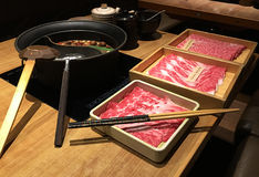 Japanese hotpot setting in a restaurant. Japanese hotpot also known as shabu shabu served with 3 different grades of wagyu beef served on a table with condiments royalty free stock image