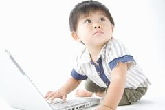 Japanese Infant. LIFESTYLE IMAGE-an infant trying to use the computer Stock Photo