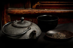 Japanese iron teapot and heap of tea leaves before mahogany back Stock Images