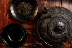 Japanese iron teapot and heap of tea leaves from top. Stock Photo