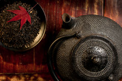 Japanese iron teapot and heap of tea leaves from top. Red maple leaf on top of tea leaves. Mahogany background. Asian culture background. Horizontal Stock Photography