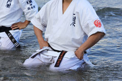 Japanese karate man sit in meditation pose on beach Royalty Free Stock Photo