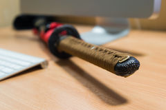Japanese katana sword on a computer table in office room Stock Photo