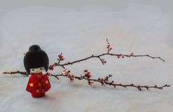 Japanese kokeshi doll and   sprig of cherry blossoms. Royalty Free Stock Photos