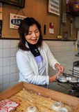 A Japanese lady Bakes a pan of Umegae Mochi Royalty Free Stock Images