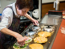 Japanese Lady Making Okonomiyaki Japanese Pancakes. An old lady in Osaka Japan, making Japanese pancakes in a restaurant she has been running for years Royalty Free Stock Image