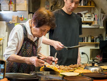Japanese Lady Making Okonomiyaki with Son. An old lady in Osaka Japan, making Japanese pancakes in a restaurant she has been running for years Stock Photos