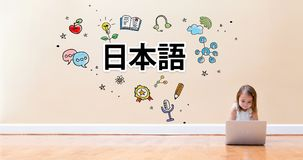Japanese Language text with little girl using a laptop computer. On floor stock images