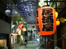 Japanese Lantern in a Shopping Arcade. A Japanese lantern hangs from the wall in a shopping arcade Stock Image