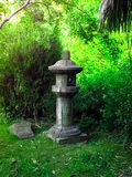 Japanese lantern in the style of Feng Shui. Japanese stone lantern in the style of Feng Shui on the green background of leaves Royalty Free Stock Photography