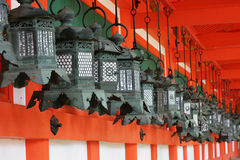 Japanese Lanterns. A row of traditional Japanese Lanterns line a wall at a temple in Nara, Japan. The scene is very Japanese in style, with red of the temple royalty free stock photo