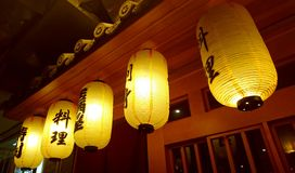 Japanese Lanterns in front of Japanese Wine and Sushi Bar. Japanese Lanterns in front of Cabinet windows with some food sample dishes inside in Japanese Wine Bar Royalty Free Stock Photos