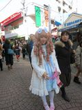 Japanese Lolita Fashion Girl on Fashion Street. A Japanese girl wearing a white lolita dress walks down a fashionable apparel street royalty free stock photos