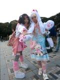 Japanese Lolita Fashion Girls Cosplaying in the Park. Two Japanese fashion girls wearing lolita fashion show off in the park. One wears bear claw gloves Royalty Free Stock Image