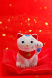 Japanese lucky cat. Greeting Japanese lucky cat in red cushion Royalty Free Stock Image