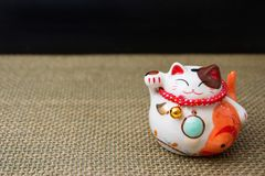 Japanese lucky cat maneki-neko on wattled fabric. Japanese lucky cat maneki-neko is a common Japanese figurine lucky charm, talisman which is often believed to stock images