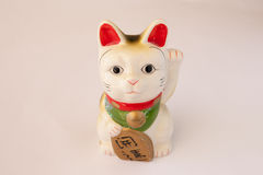 Japanese Lucky Cat. Red, White, Green and Gold Japanese Lucky Cat waving one paw in the air and holding a lucky tablet with the other royalty free stock image