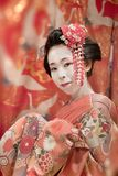 Japanese Maiko or geisha in red kimono coifed hair brooch with p Stock Photo
