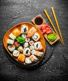 Japanese maki, rolls and sushi with ginger, soy sauce and wasabi. On black rustic background royalty free stock photos