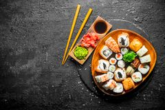 Japanese maki, rolls and sushi with ginger, soy sauce and wasabi. On black rustic background stock image