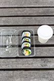 Japanese maki rolls. With tuna, crabsticks, egg and greens in plastic lunch box on the wood table. Coffee cup. Lunch conception Royalty Free Stock Photography