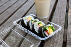Japanese maki rolls. With tuna, crabsticks, egg and greens in plastic lunch box on the wood table. Coffee cup. Lunch conception Stock Images
