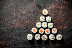 Japanese Maki sushi with salmon, cucumber and chicken. On dark rustic background royalty free stock photo