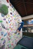 A Japanese man climbing a rock wall indoor. Stock Photos