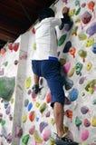 A Japanese man climbing a rock wall indoor. Stock Images