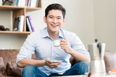 Japanese man drinking coffee in his living room stock images