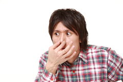 Japanese man holding his nose because of a bad smell. Studio shot of young Japanese man on white background stock photography