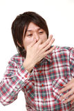 Japanese man holding his nose because of a bad smell. Studio shot of young Japanese man on white background royalty free stock photography