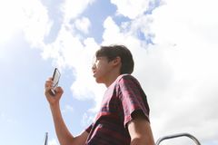 A Japanese man with a smart phone in hands on sky background royalty free stock photo