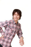 Japanese man suffers from lumbago . Studio shot of young Japanese man on white background Royalty Free Stock Photos