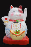 Japanese maneki neko lucky welcoming cat. On black background Royalty Free Stock Photos