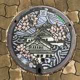 Osaka, Japan: sewer cap / manhole cover / hatch, Japanese language means Osaka royalty free stock image