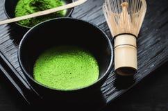 Japanese matcha green tea at homemade clay bowl with bamboo whisk. Japanese matcha green tea and matcha green tea powder at homemade clay bowl with bamboo whisk royalty free stock images