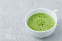 Japanese matcha green tea latte in white cup on gray background Royalty Free Stock Photos