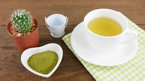 The Japanese matcha green tea powder on ceramic heart shaped bowl and cup of hot green tea with cotton fabric Stock Image